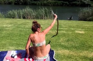A Girl Catches a Cobra Fearlessly while Taking Sun Bath